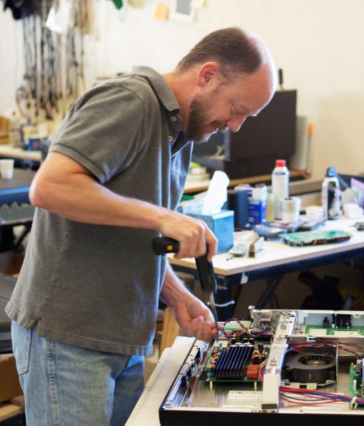 Kim repairing a TV in Albuquerque